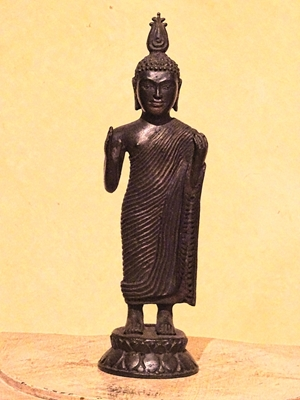 Standing Buddha from Sri Lanka wearing monastic robe (Utterasangha) eyes open and looking straight with hands semi stretched. ca 19th to 20th century